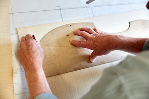 A violin maker's workshop. Skilled craftsman drawing around the outline of a wood back board for a vの写真素材 [FYI02705926]