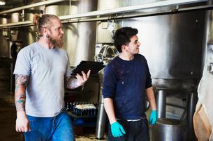 Two men working in a brewery, walking past large metal kettles, holding digital tablet.の写真素材 [FYI02705941]