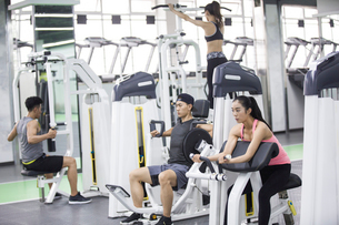 Young adult using exercise machine at gymの写真素材 [FYI02705947]