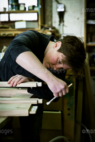A woman working in a furniture maker's workshop using a small brush to apply glue to the wood.の写真素材 [FYI02705949]