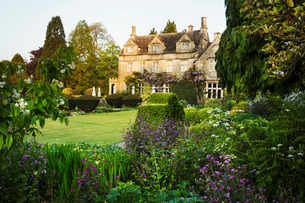 Exterior view of a 17th century country house from a garden with flower beds, shrubs and trees.の写真素材 [FYI02705952]