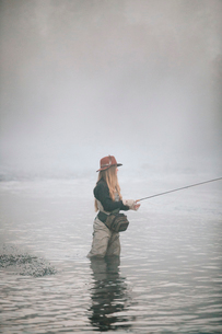 A woman fisherman fly fishing, standing in waders in thigh deep water.の写真素材 [FYI02705962]
