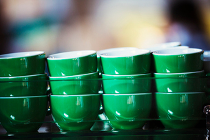 Specialist coffee shop. Green coffee cups stacked up.の写真素材 [FYI02705965]