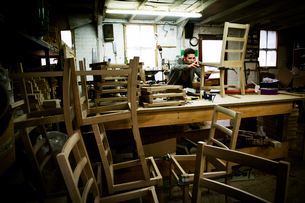 A man working in a furniture maker's workshop assembling a chair.の写真素材 [FYI02705970]