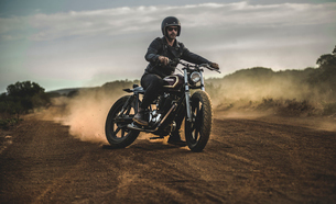 Man wearing open face crash helmet and sunglasses riding cafe racer motorcycle on a dusty dirt road,の写真素材 [FYI02705971]