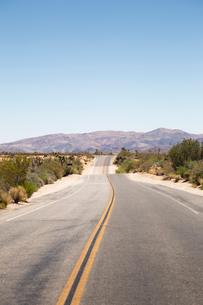 USA, California, Joshua Tree, Road leading towards mountain range on horizonの写真素材 [FYI02705973]