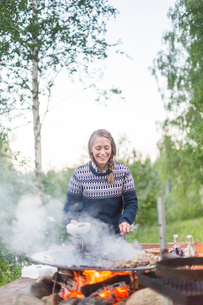A woman cooking on a fire pitの写真素材 [FYI02705976]