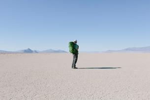 Male backpacker hiking in vast desert, Black Rock Desert, Nevadaの写真素材 [FYI02705992]