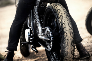 Rear view of man sitting on cafe racer motorcycle on a dusty dirt road, close up of tire.の写真素材 [FYI02705998]