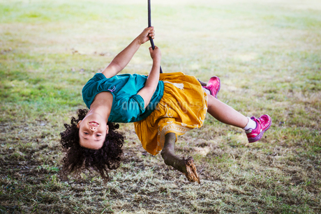 Girl sitting on a tree swing, upside down, smiling at camera.の写真素材 [FYI02706007]