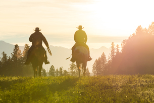 Two cowboys riding on horseback in a Prairie landscape at sunset.の写真素材 [FYI02706010]