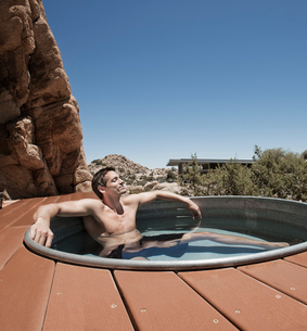 A man on the terrace of an eco home, a low impact house in the desert landscape, in a sunken hot tubの写真素材 [FYI02706014]