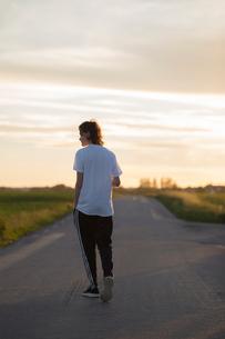Teenage boy walking down a rural road in Laholm, Swedenの写真素材 [FYI02706017]