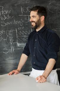 Baker standing in front of a blackboard with a recipe for bread written on it.の写真素材 [FYI02706021]