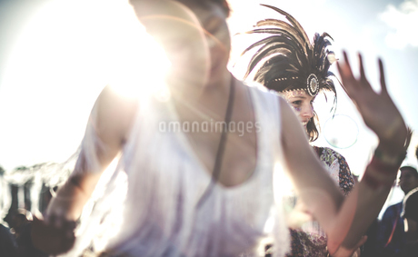 Young woman at a summer music festival dancing among the crowd.の写真素材 [FYI02706022]