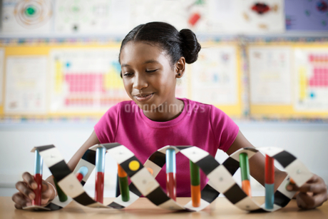 A girl in a science class holding a model of a helix structure.の写真素材 [FYI02706029]