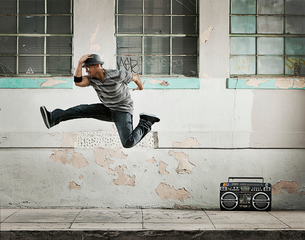 A young man breakdancing, leaping in the air doing a karate kick on a city street.の写真素材 [FYI02706030]
