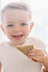Portrait of a smiling young boy eating a sandwich.の写真素材 [FYI02706033]