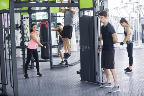 Young adult using exercise machine at gymの写真素材 [FYI02706056]