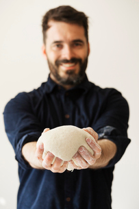 Baker holding a portion of bread dough shaped into a ball.の写真素材 [FYI02706062]
