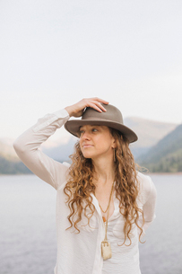 A woman in a wide brimmed hat by a mountain lake.の写真素材 [FYI02706065]