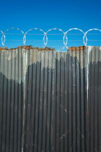 Worn corrugated metal fence, razor wire above.の写真素材 [FYI02706083]