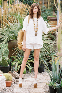 A young woman in white shirt and shorts wearing platform heels.の写真素材 [FYI02706101]
