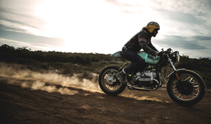 Side view of man wearing crash helmet riding cafe racer motorcycle on a dusty dirt road.の写真素材 [FYI02706106]