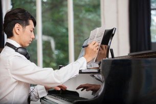 Young man sitting at a grand piano in a rehearsal studio, annotating sheet music.の写真素材 [FYI02706124]