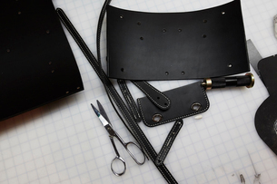 A handmade blue leather bag, strap, component part parts, scissors and hand tools.の写真素材 [FYI02706147]