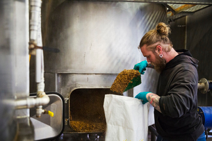 Man scraping shovelling spent grain from a large kettle into a bag in a brewery.の写真素材 [FYI02706148]
