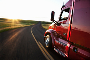 Close up side view looking forward of a  commercial truck on a highway at sunset.の写真素材 [FYI02706154]