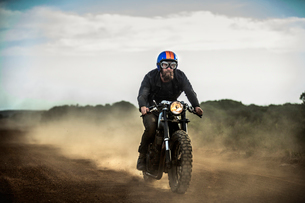 Man wearing open face crash helmet and goggles riding cafe racer motorcycle on a dusty dirt road.の写真素材 [FYI02706158]