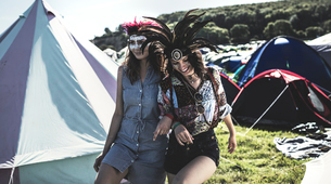 Two young women at a summer music festival faces painted, wearing feather headdresses, walking arm iの写真素材 [FYI02706159]