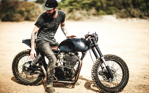 Side view of bearded man with tattoos on his arms sitting on cafe racer motorcycle on a dusty dirt rの写真素材 [FYI02706162]