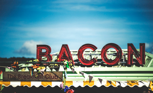 Food stall at a summer music festival red neon sign advertising bacon.の写真素材 [FYI02706171]