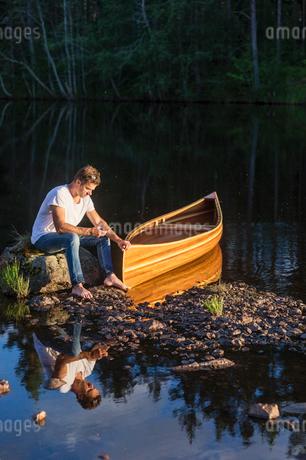 Sweden, Vastmanland, Hallefors, Bergslagen, Man sitting on boulder in middle of lakeの写真素材 [FYI02706185]