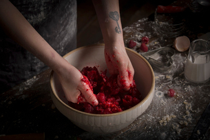 Valentine's Day baking, woman preparing fresh raspberries in a bowl.の写真素材 [FYI02706186]