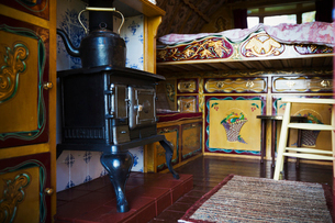 A cast iron stove with large metal kettle, a mantlepiece and storage cupboards and raised bed, the iの写真素材 [FYI02706191]
