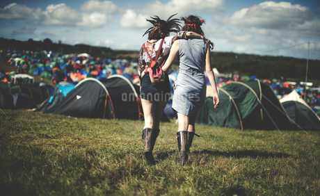 Rear view of two young women at a summer music festival wearing feather headdresses, walking arm inの写真素材 [FYI02706199]