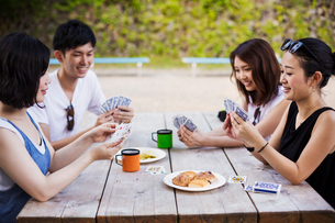 Three young women and a man sitting at a table, playing cards.の写真素材 [FYI02706202]