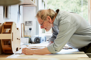 A violin maker at his drawing board drawing out the plans and outline for a new instrument.の写真素材 [FYI02706238]