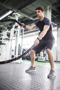 Young man exercising with battling rope at gymの写真素材 [FYI02706239]