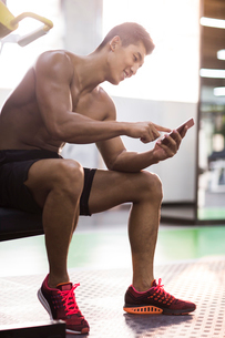 Young man using smart phone in gymの写真素材 [FYI02706263]