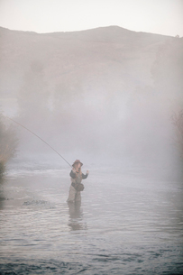 A woman fisherman fly fishing, standing in waders in thigh deep water.の写真素材 [FYI02706282]