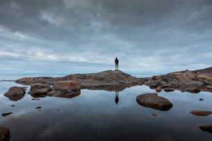 Woman standing on rock by a lake in Vasterbotten, Swedenの写真素材 [FYI02706284]
