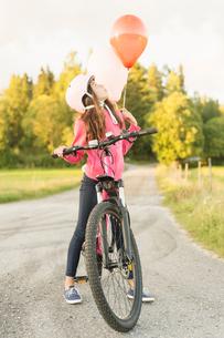 Sweden, Vastmanland, Hallefors, Bergslagen, Girl (10-11) riding bicycle at sunsetの写真素材 [FYI02706286]