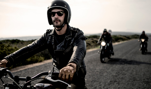 Man wearing open face crash helmet and sunglasses riding cafe racer motorcycle along rural road.の写真素材 [FYI02706296]