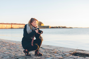 Woman holding a camera by the seaの写真素材 [FYI02706297]