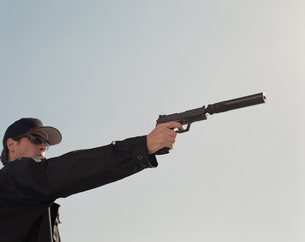 Man in special forces, aiming high powered hand gun with silencer attachedの写真素材 [FYI02706298]